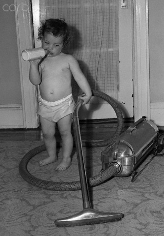 Baby boy (12-23 months) cleaning with vacuum cleaner