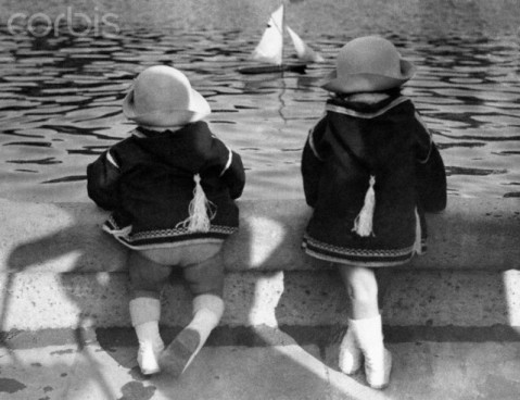 Twin girls (6-7) looking at model sailboat in pond