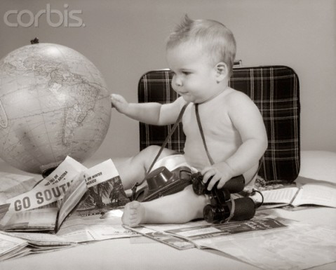 1960s Baby Seated Looking At Globe With Camera Binoculars Suitcase and Travel Brochures