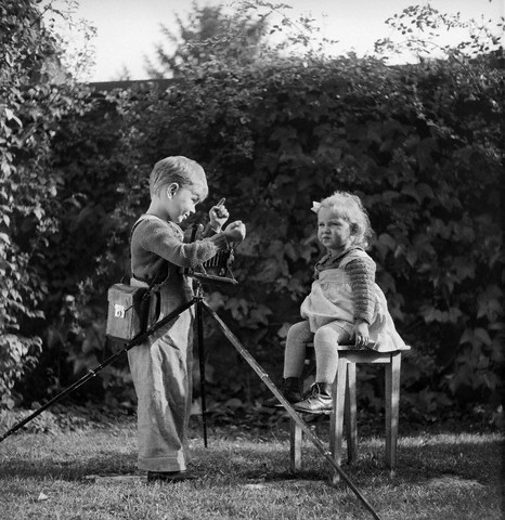 1930s 1940s Boy With Camera On Tripod Taking Photograph Of Baby Girl Toddler Sitting On Stool