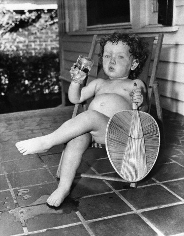 Girl (2-3 years ) sitting on lounge chair with drink and fan