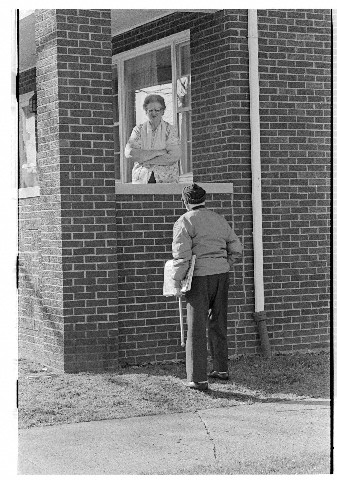 Man Speaking to a Woman on Her Porch
